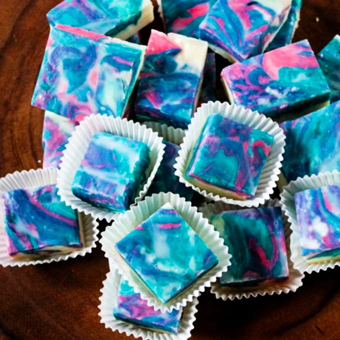 UNICORN FUDGE - Top down view of pink and blue cotton candy flavored unicorn fudge in white cupcake liners.
