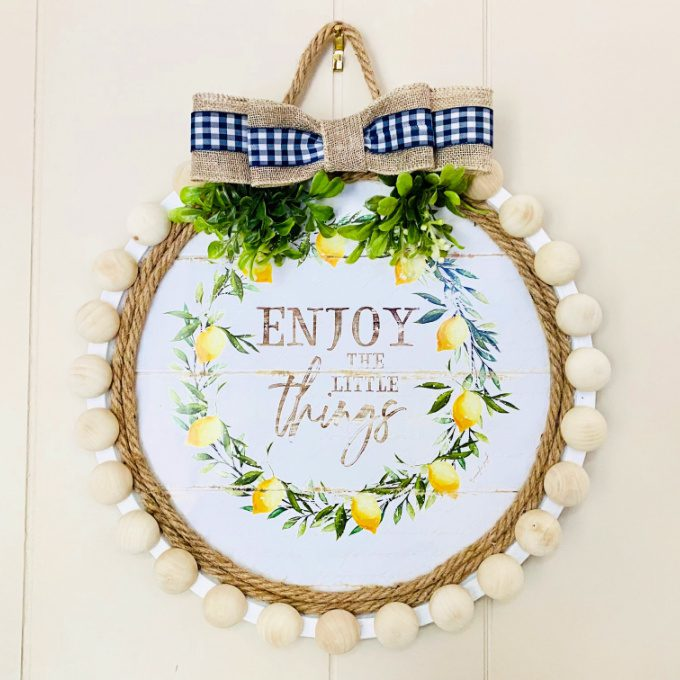Image contains a pizza pan wreath with a burlap ribbon and wooden beaded edge.