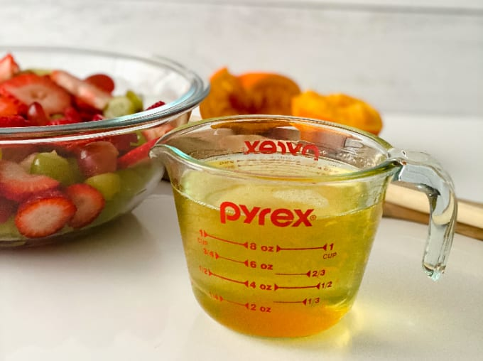 Image contains a Pyrex measuring cup filled with orange juice dressing.