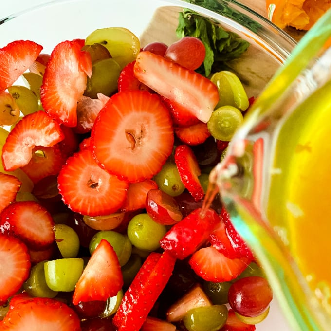 Close up, top down image of fruit salad being dressed with orange juice dressing.