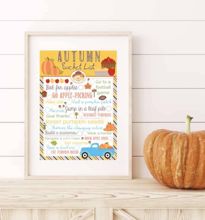 Framed autumn bucket list next to a pumpkin.