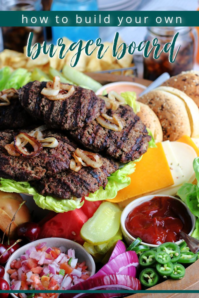 How to build your own burger board piled high with grilled burgers, toasted buns, condiments, cheeses and all your other favorite toppings!This board is perfect for parties and summer grilling. via @jugglingactmama