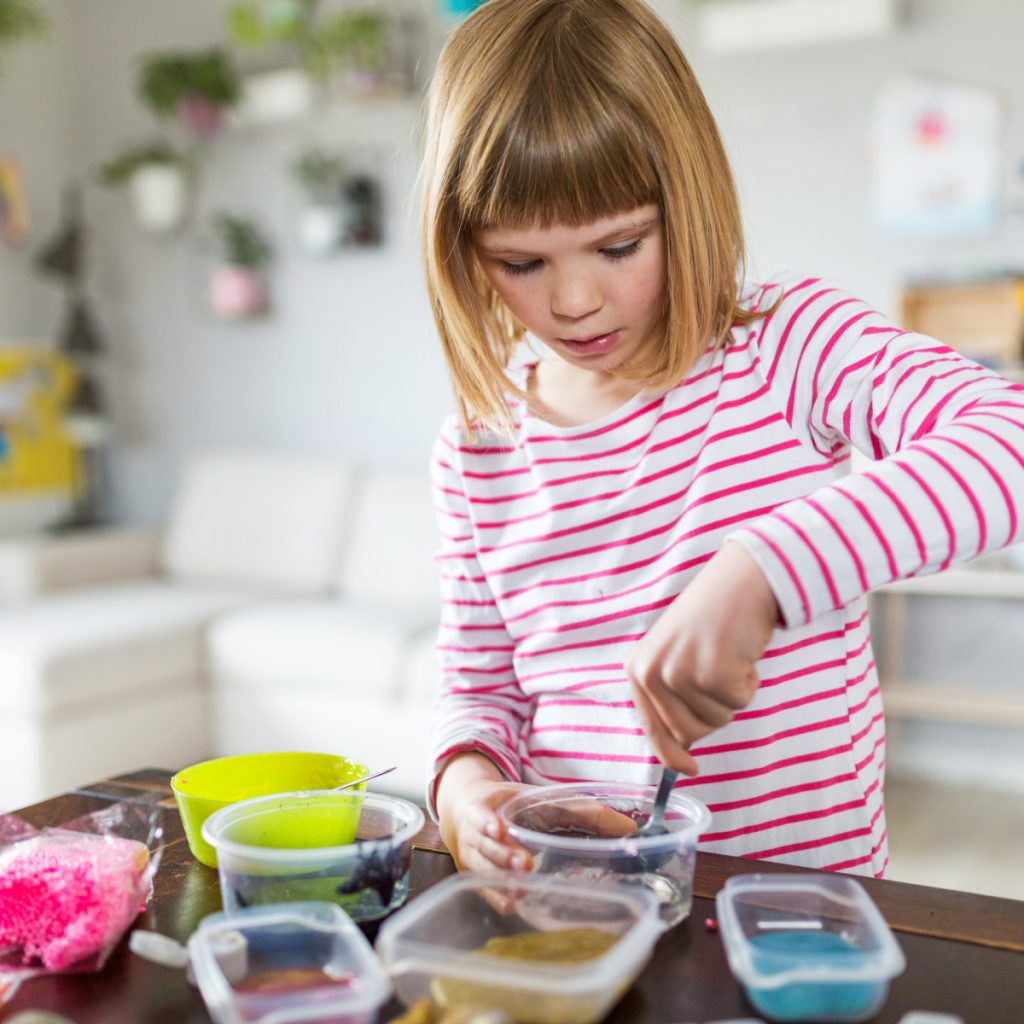 Child mixing slime in small bowls.