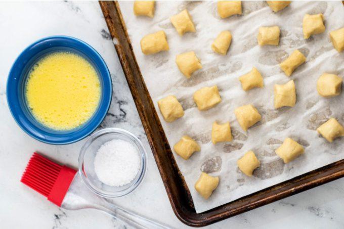 Ingredients to make pretzel bites - butter, salt, and frozen dough on a sheet pan.