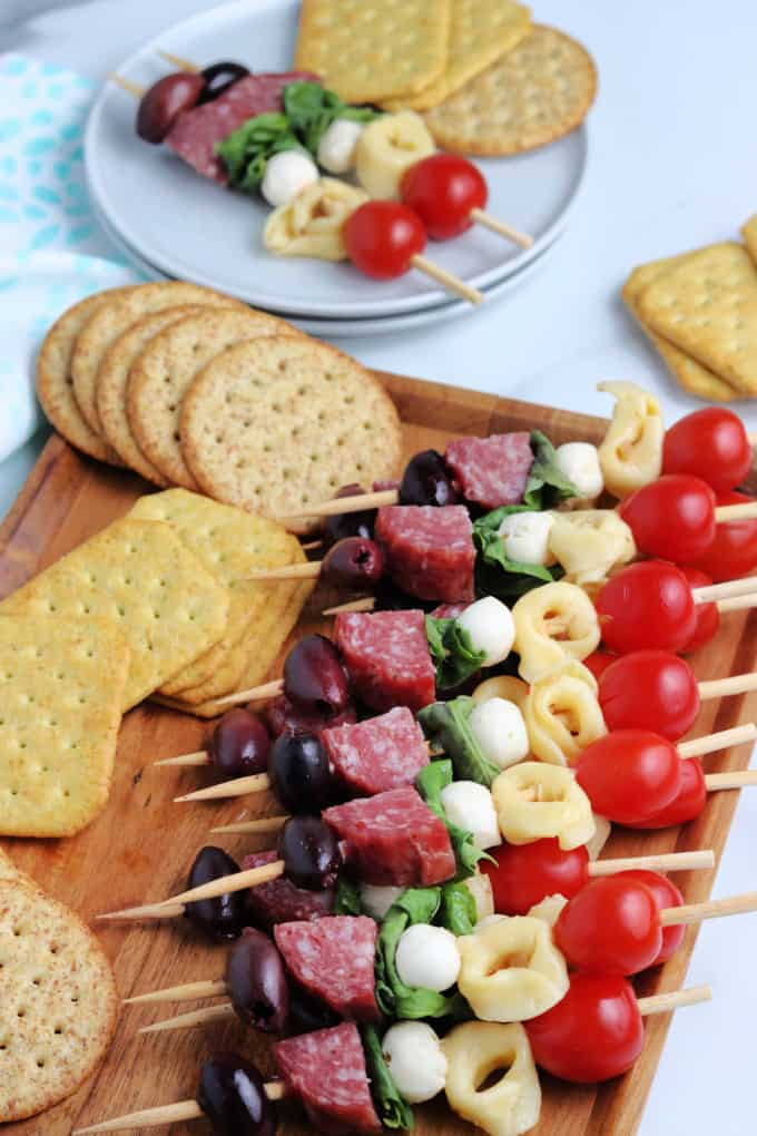 Antipasto Kabobs along with a variety of crackers on a wood cutting board.