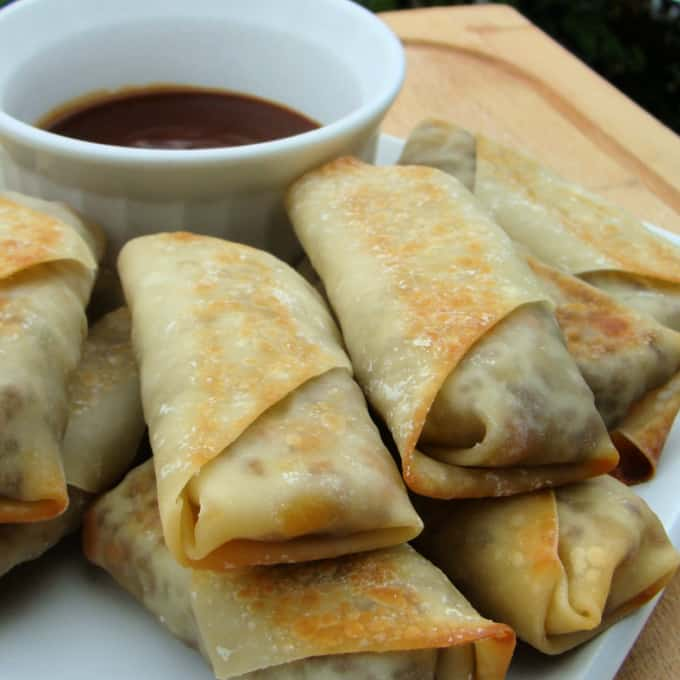 Square image of baked eggrolls stacked on a white plate with a ramekin of dipping sauce.