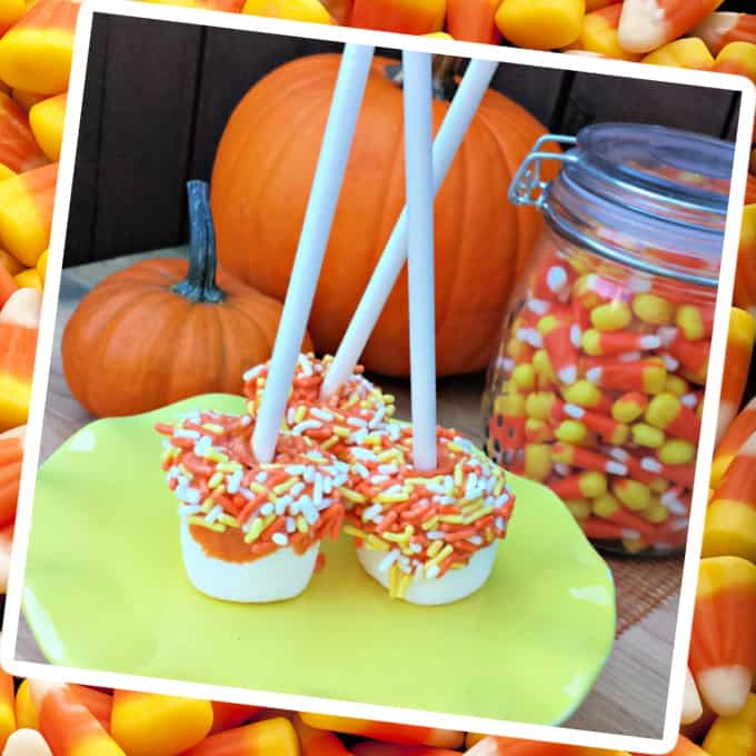 a photo of candy corn marshmallow pops on a candy corn background