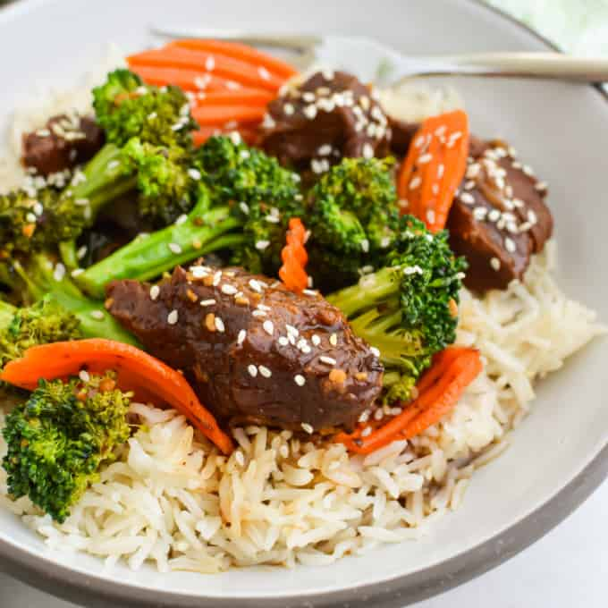 Square image of beef, broccoli and carrots on top of a bed of rice and topped with sesame seeds.