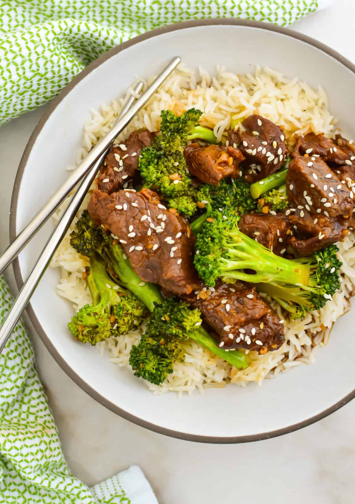 Close up, top down image of slow cooker beef and broccoli on top of rice on a white plate with metal chopsticks.