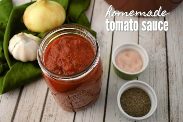 tomato sauce in a canning jar next to an onion, garlic bulb and seasonings