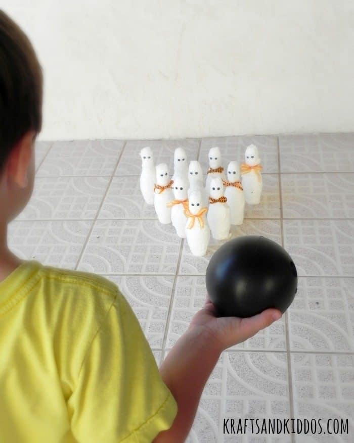 Child holding a small plastic bowling ball in front of 10 mummy bowling pins.