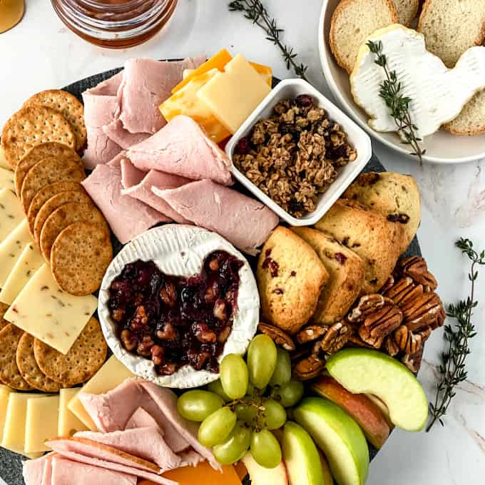 Square image of baked brie at the center of a charcuterie board, surrounded by meats, cheeses, fruit, and crackers.